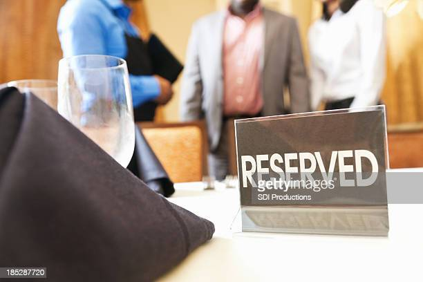 Reserved sign closeup while guests are being directed to table