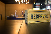 Reserved sign on top of a wooden table in a restaurant.