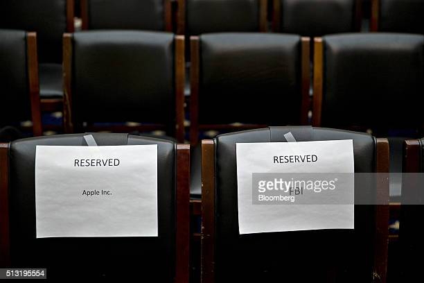 Reserved signs for Apple Inc and the Federal Bureau of Investigation hang on chairs inside the House Judiciary Committee hearing room in Washington...