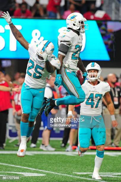 Reshad Jones of the Miami Dolphins is congratulated by Xavien Howard after an interception against the Atlanta Falcons at MercedesBenz Stadium on...