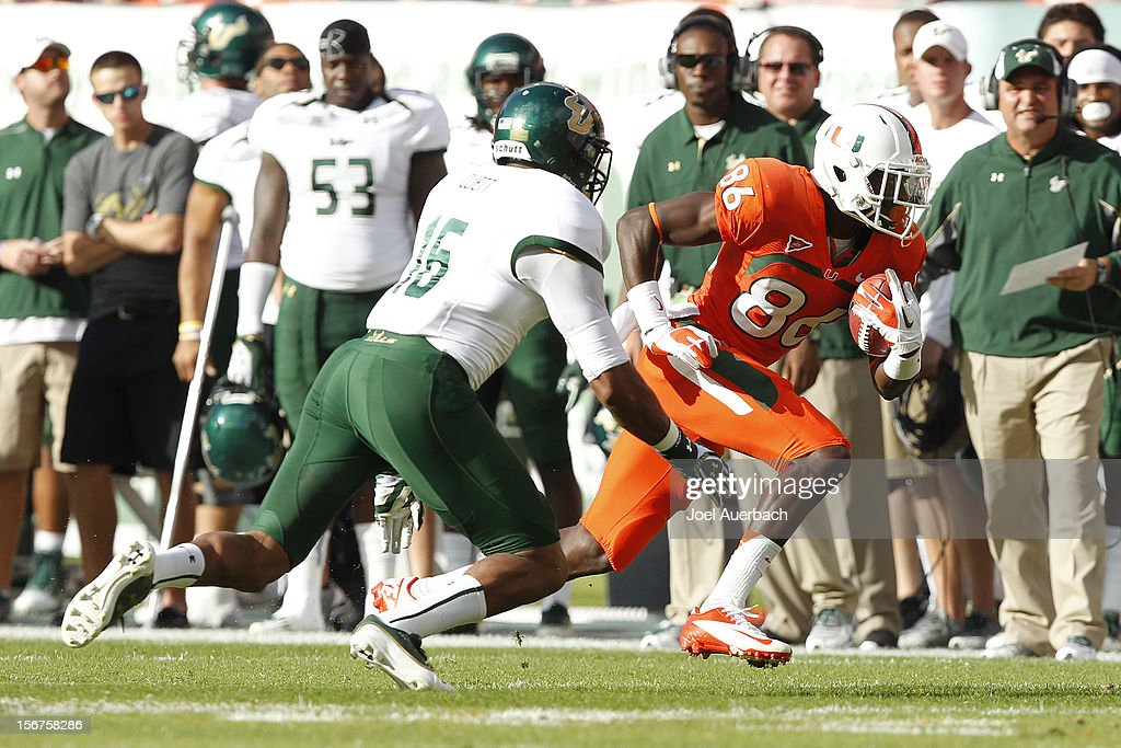 Reshard Cliett #16 of the South Florida Bulls pursues Herb Waters #86 of the Miami Hurricanes as he runs with the ball on November 17, 2012 at Sun Life Stadium in Miami Gardens, Florida. The Hurricanes defeated the Bulls 40-9.