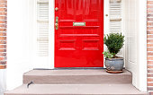 red door and potted plant on the stairs