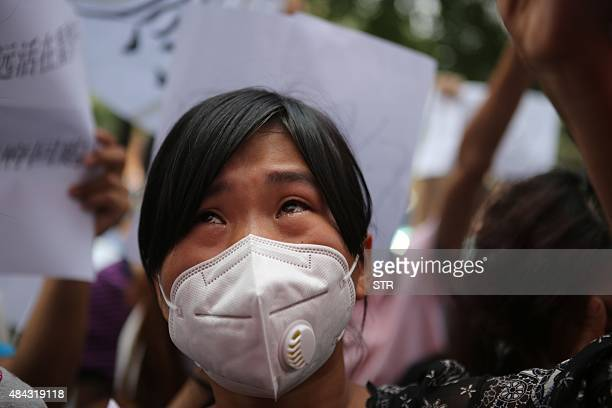 A resident affected by the explosions that hit a nearby chemical warehouse last week cries as she joins a protest outside the hotel where authorities...