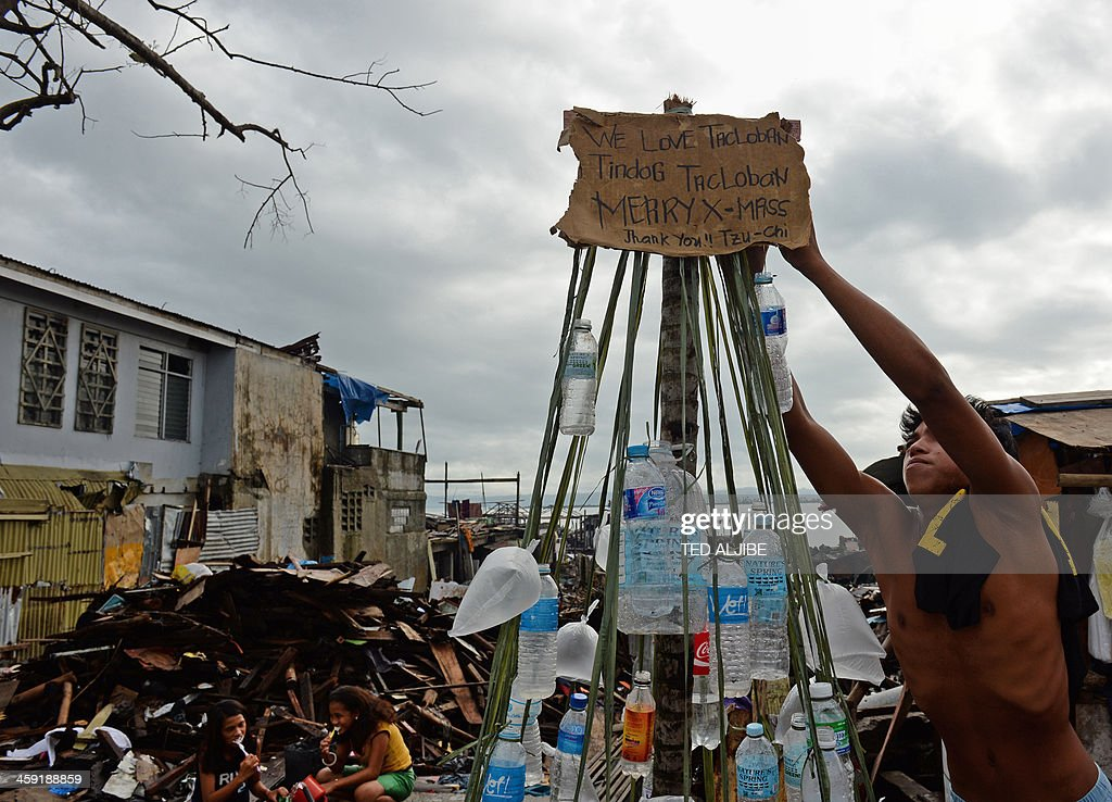 A resident and survivor of Super Typhoon Haiyan decorates a makeshift Christmas tree made up of plastic bottles and displayed along a street in the coastal area of Tacloban, Leyte province, on December 24, 2013, on the eve of Christmas. Philippine survivors of one of the strongest typhoons to hit land defiantly got ready December 24, to celebrate Christmas atop their ruined communities. Haiyan's ferocious 315 kilometres (195 miles) an hour winds flattened the gritty neighbourhood on Tacloban's coast, called Magallanes, then swept up everything else with giant waves in a day of terror on November 8.