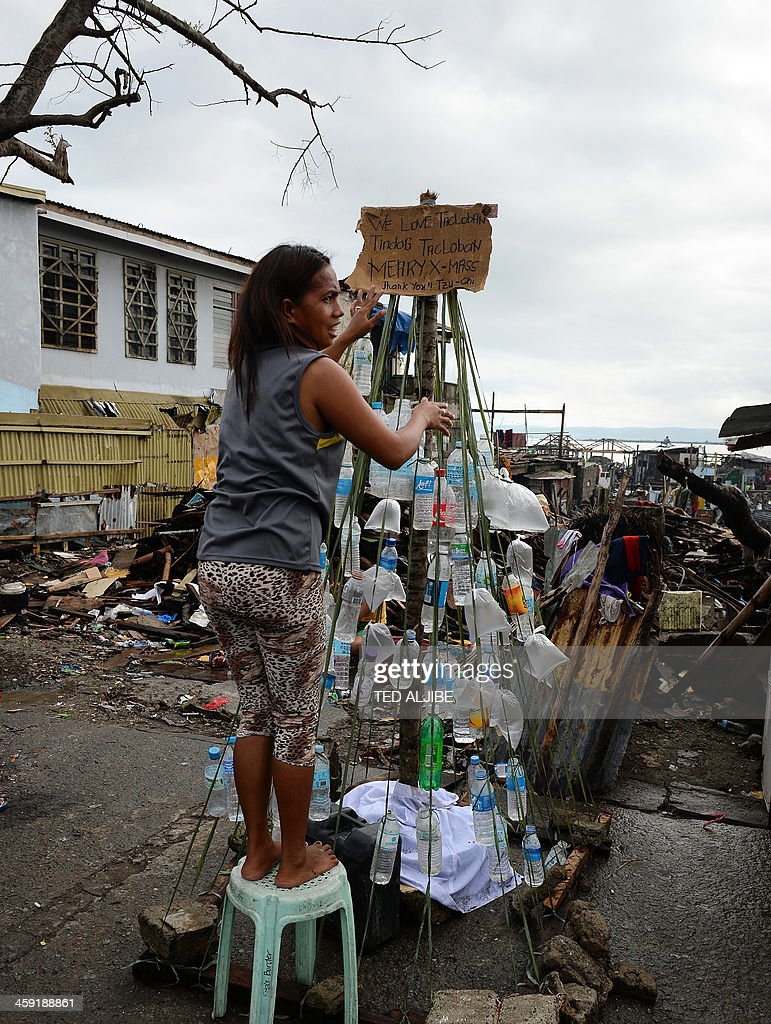 A resident and survivor of Super Typhoon Haiyan decorates a makeshift Christmas tree made up of plastic bottles and displayed along a street in the coastal area of Tacloban, Leyte province, on December 24, 2013, on the eve of Christmas. Philippine survivors of one of the strongest typhoons to hit land defiantly got ready December 24, to celebrate Christmas atop their ruined communities. Haiyan's ferocious 315 kilometres (195 miles) an hour winds flattened the gritty neighbourhood on Tacloban's coast, called Magallanes, then swept up everything else with giant waves in a day of terror on November 8. AFP PHOTO / TED ALJIBE