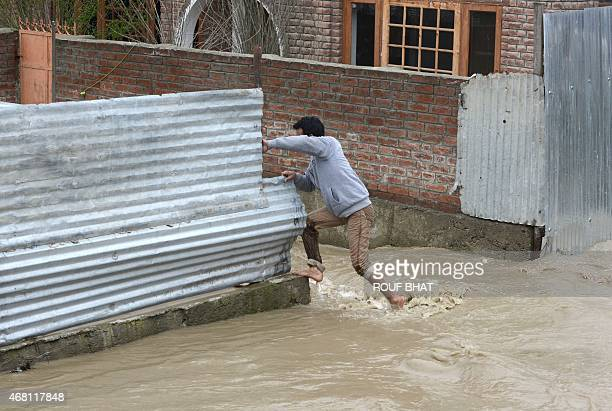 A resident attempts to reach his inundated home as waters rise in a neighbourhood of Srinagar on March 30 2015 At least 10 people have been buried by...