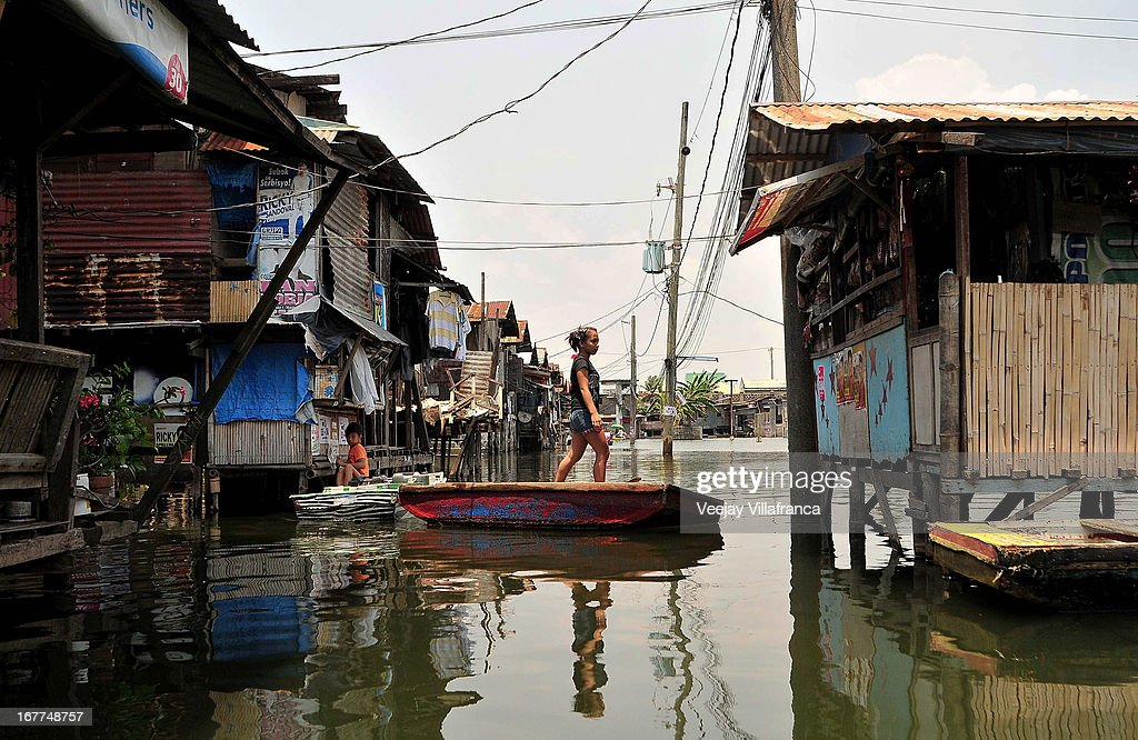 A resident balances rides in a makeshift boat in the waterways of Artex Compound in Malabon City on April 28, 2013 in Manila, Philippines. The residents of the former textile compound had to adjust their daily lives after flood waters submerged their low-lying village in 2004.