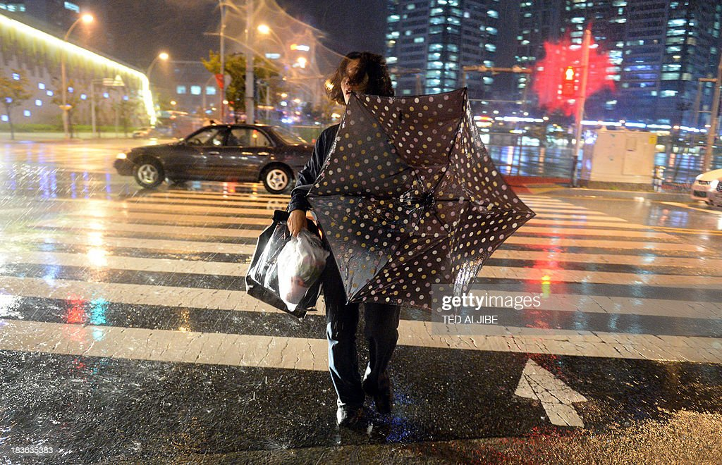 A resident brave strong gale and heavy rains brought about by Typhoon Danas in Busan on October 8, 2013, before the typhoon is expected to pass through the coastal city. Packing winds of up to 180 kilometres (112 miles) per hour near its centre, Danas was churning northwest towards the southern Okinawa island chain and was expected to reach a point off the western coast of Kyushu island by early on October 9.