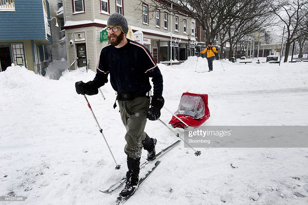 Resident Brian Postlewaite tows his son, Fraser Postlewaite, 2, across Holland Street after Winter Storm Nemo in Somerville, Massachusetts, U.S., on Saturday, Feb. 9, 2013. More than two feet of snow fell on parts of the U.S. Northeast as high winds left hundreds of thousands of people in the region without power, closed highways and forced the cancellation of 4,700 flights. Photographer: Kelvin Ma/Bloomberg via Getty Images