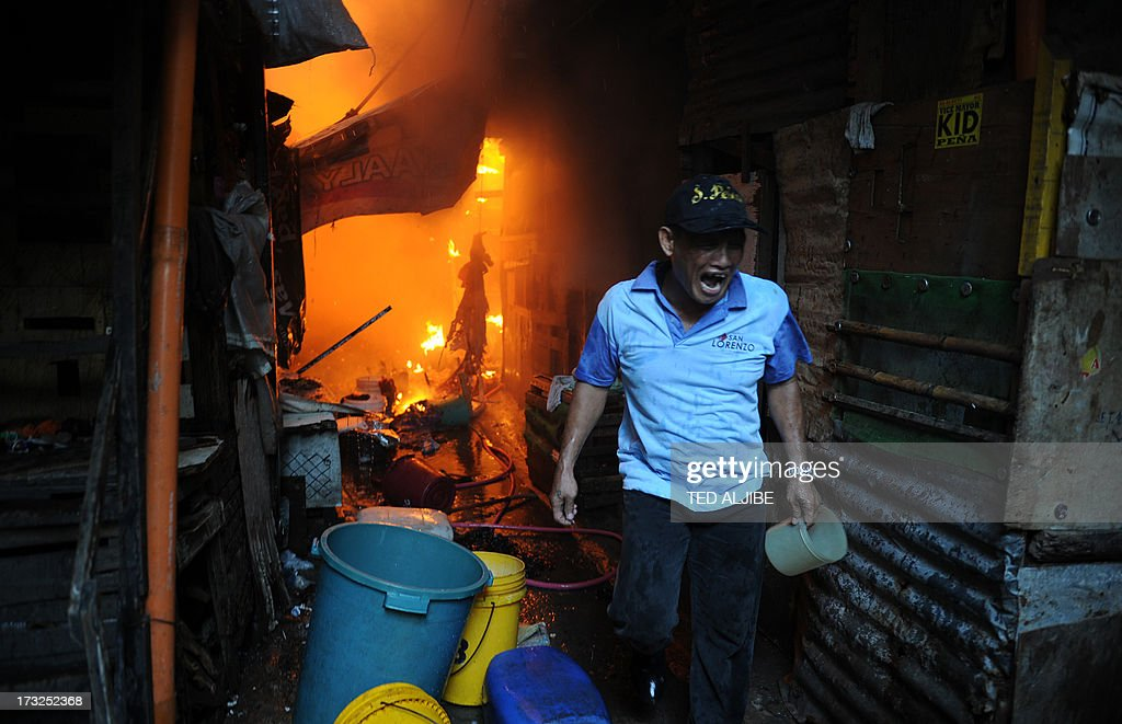 A resident calls out for firefighters as a fire engulfs a shanty town in the financial district of Manila on July 11, 2013, leaving more than 1,000 people homeless according to city officials. There were no immediate reports of casualties from the blaze, which occurred mid-morning amid government plans to relocate thousands of families living in areas vulnerable to floods and typhoons.
