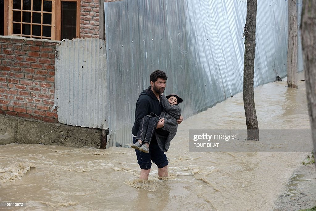 A resident carries a child through rising waters in a neighbourhood of Srinagar on March 30 2015 At least 10 people have been buried by mudslides and...