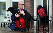 A resident carries a dog along a flooded street in Carlisle northern England on December 6 2015 One man was killed yesterday as Storm Desmond whipped...