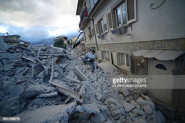TOPSHOT A resident carries a pram among damaged buildings after a strong earthquake hit Amatrice on August 24 2016 Central Italy was struck by a...