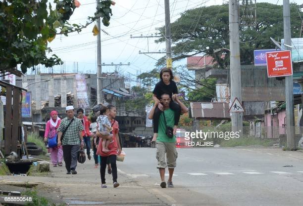 TOPSHOT A resident carries a relative as they evacuate from their homes in Marawi in southern island of Mindanao on May 27 after government planes...