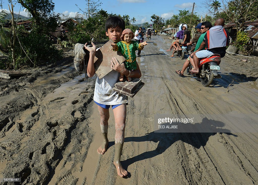 A resident carries a religious statue along a muddy road in the town of New Bataan, compostela province on December 6, 2012. Nearly 200,000 people are homeless and more than 300 dead after the Philippines suffered its worst typhoon this year, authorities said on December 6, reaching out for international aid to cope with the scale of the disaster. AFP PHOTO / TED ALJIBE