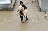 A resident carries a sheep through waters as they rise in a neighbourhood of Srinagar on March 30 2015 At least 10 people have been buried by...