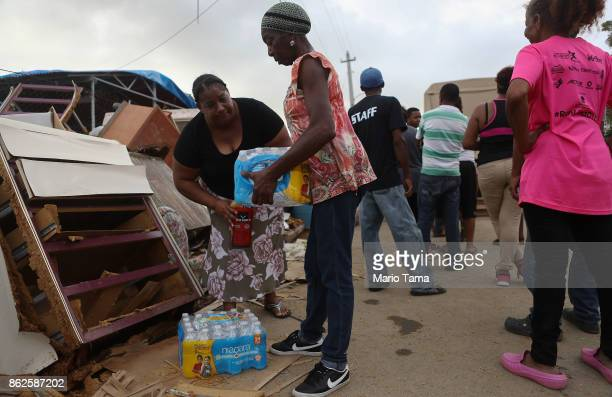 A resident carries bottled water provided by FEMA in a neighborhood without grid electricity or running water on October 17 2017 in San Isidro Puerto...