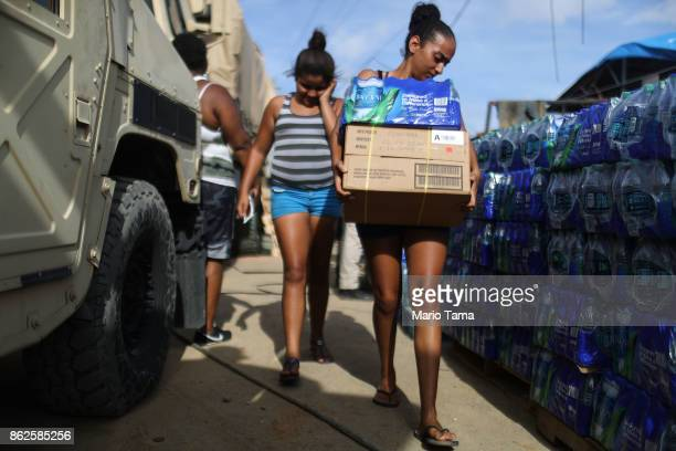 A resident carries food and water provided by FEMA in a neighborhood without grid electricity or running water on October 17 2017 in San Isidro...