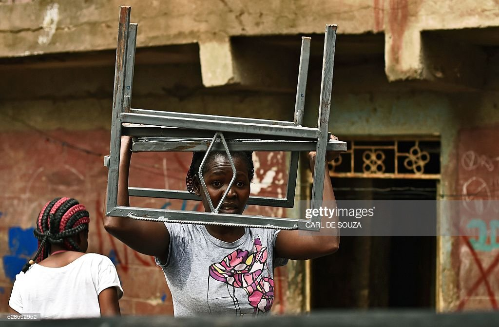 A resident carries her belongings from a block of flats which is going to be demolished on May 6, 2016. Following a building collapse which claimed at least 40 lives with more 80 people still unaccounted for, after severe flooding, the government has ordered the demolition of similar unsafe buildings in the area. Located in the poor, tightly-packed Huruma neighbourhood, the building, which housed around 150 families crammed into single rooms, had been slated for demolition after being declared structurally unsound. But an evacuation order for the structure, which was built next to a river just two years ago, was ignored. / AFP / CARL