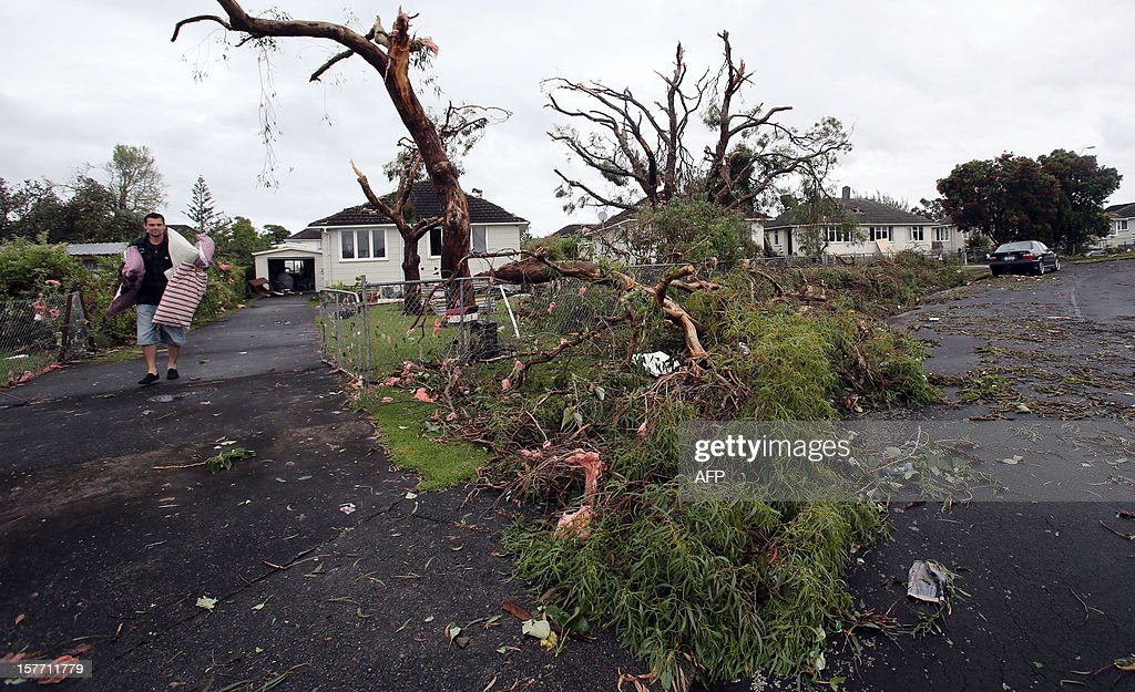 A resident carries his belongings amogst debris as he leaves his damaged house for the night in Hobsonville, Auckland on December 6, 2012 after packed wind gusts of up to 110 kilometres (70 miles) per hour, struck suburban Hobsonville in the afternoon. A freak storm described by police as a tornado hit New Zealand's largest city Auckland on December 6 causing 'utter devastation', with three people reportedly killed in ferocious winds. AFP PHOTO / Michael Bradley