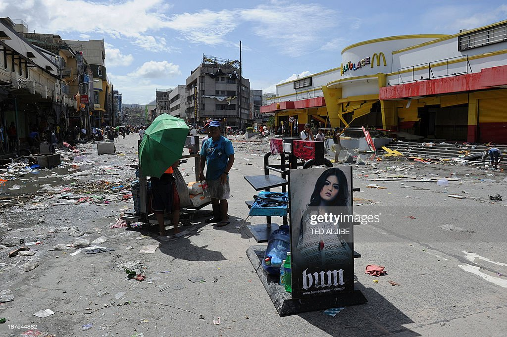 Resident carry looted goods in Tacloban City, Leyte province, central Philippines on November 10, 2013, three days after devastating Typhoon Haiyan hit the city on November 8. The death toll from a super typhoon that decimated entire towns in the Philippines could soar well over 10,000, authorities warned on November 10, making it the country's worst recorded natural disaster.