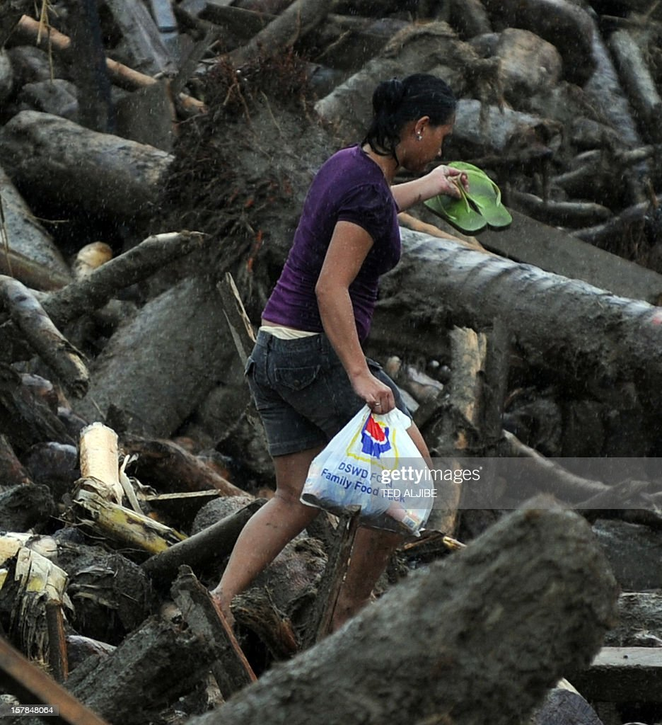 A resident carrying a bag full of relief goods walks amongst typhoon debris as she heads for her home in New Bataan, Compostela Valley province on December 7, 2012. President Benigno Aquino vowed action on the Philippines' typhoon disasters December 7 as bruised and grieving survivors tried to recover from the latest that left nearly 500 people dead. AFP PHOTO/TED ALJIBE