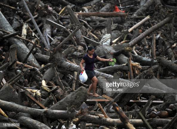 A resident carrying a bag full of relief goods walks amongst typhoon debris as she heads for her home in New Bataan Compostela Valley province on...