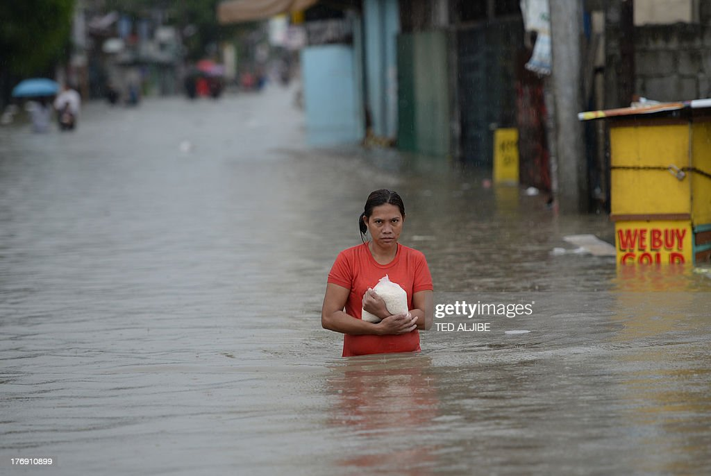 A resident carrying a plastic bag of rice wades through a flooded street in Cavite, southwest of Manila on August 19, 2013. Torrential rain paralysed large parts of the Philippine capital August 19, as neck-deep water swept through homes, while floods in northern farming areas claimed at least one life.