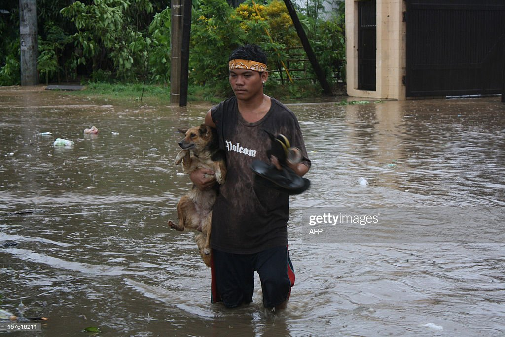A resident carrying his pet dog wades through a flooded street due to heavy rains brought about by Typhoon Bophal in Cagayan de Oro City, southern island of Mindanao on December 4, 2012. Typhoon Bopha smashed into the southern Philippines early December 4, as more than 40,000 people crammed into shelters to escape the onslaught of the strongest cyclone to hit the country this year. AFP PHOTO