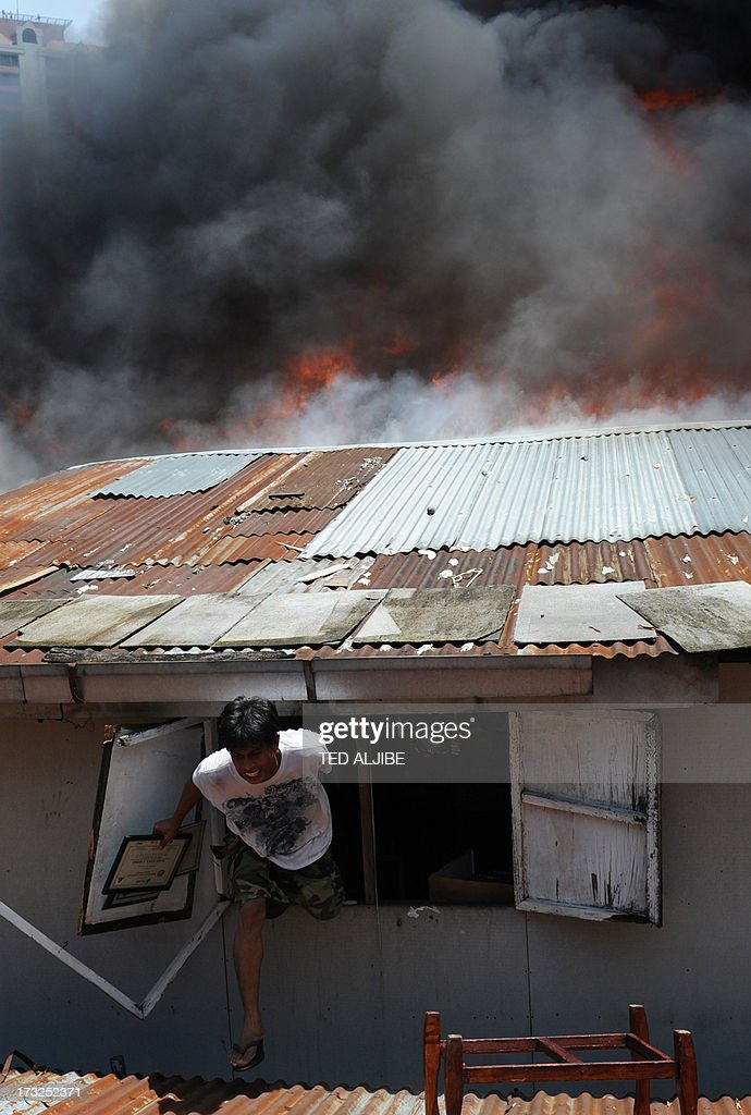 A resident (C) carrying salvaged belongings escapes out of a window of his burning house as a fire engulfs a shanty town in the financial district of Manila on July 11, 2013, leaving more than 1,000 people homeless according to city officials. There were no immediate reports of casualties from the blaze, which occurred mid-morning amid government plans to relocate thousands of families living in areas vulnerable to floods and typhoons.