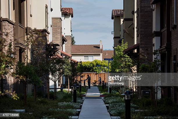 A resident checks his mobile phone as a woman pushes a baby carriage in the Pulte Homes Inc Pepper Lane development in San Jose California US on...