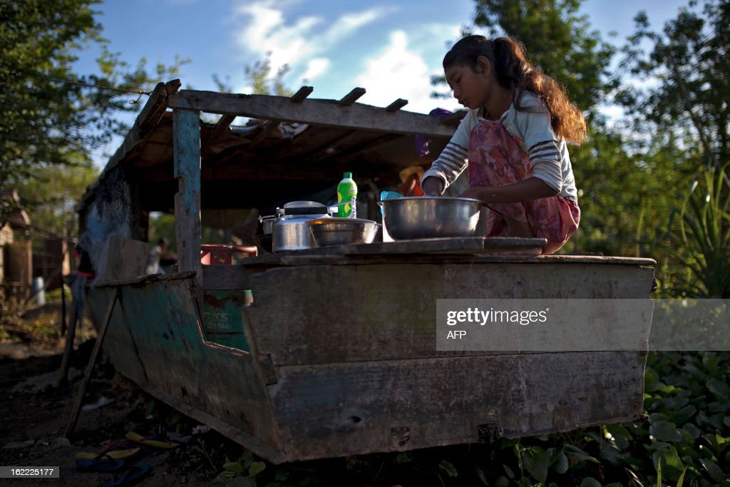 A resident cleans her dishes, in Tanjung Labian, near the location where suspected Philippine militants are holding off on February 21, 2013. Followers of a Philippine sultan who crossed to the Malaysian state of Sabah this month will not leave and are reclaiming the area as their ancestral territory, the sultan said on February 17 amid a tense stand off. AFP PHOTO / MOHD RASFAN