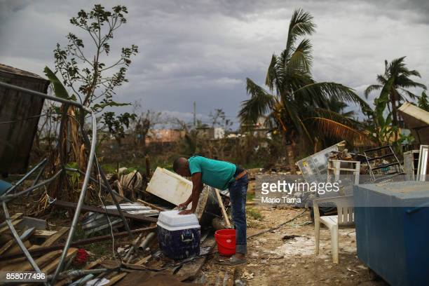 A resident cleans outside his home about two weeks after Hurricane Maria swept through the island on October 5 2017 in San Isidro Puerto Rico...