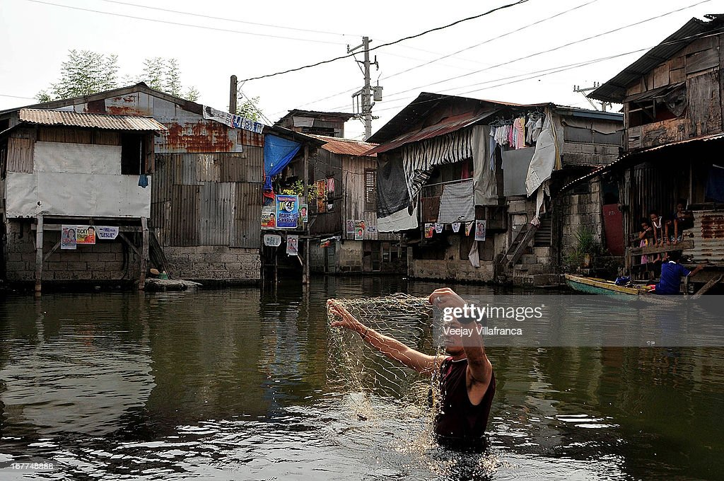 A resident collects his fishnet in the floodwaters of Artex Compound in Malabon City on April 28, 2013 in Manila, Philippines. The residents of the former textile compound had to adjust their daily lives after flood waters submerged their low-lying village in 2004.