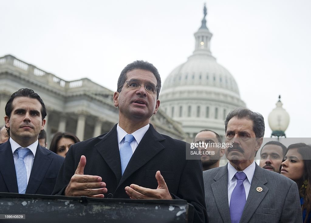 Resident Commissioner Pedro Pierluisi (C) of Puerto Rico speaks alongside US Representative Jose Serrano (R), Democrat of New York, and Puerto Rican activists, urging Congress to allow an end to the island's territorial status, during a press conference at the US Capitol in Washington, DC, on January 15, 2013. AFP PHOTO / Saul LOEB
