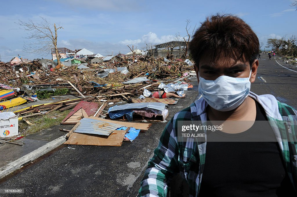 A resident covering his face with a mask rides past dead bodies littered along a road in Tacloban, on the eastern island of Leyte on November 10, 2013 after Super Typhoon Haiyan swept over the Philippines. The typhoon that destroyed entire towns across the Philippines is believed to have killed more than 10,000 people, authorities said on November 10, which would make it the country's deadliest recorded natural disaster.