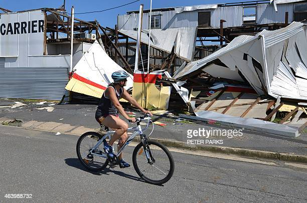 A resident cycles past a cyclone damaged business in the northern Queensland town of Rockhampton on February 21 2015 Australia was assessing the...