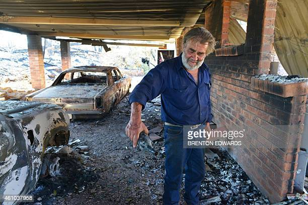 Resident David Miller pours the remains from a wine bottle that melted in the intensity of the heat when his home near Kersbrook was destroyed by a...