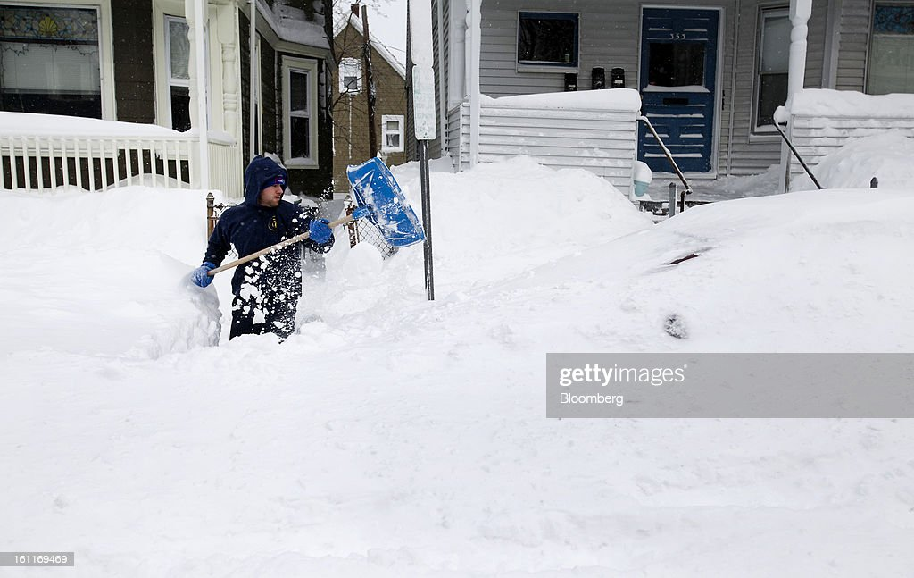 Resident Devin Romanul shovels his wife's car out of the snow on Highland Avenue after Winter Storm Nemo in Somerville, Massachusetts, U.S., on Saturday, Feb. 9, 2013. More than two feet of snow fell on parts of the U.S. Northeast as high winds left hundreds of thousands of people in the region without power, closed highways and forced the cancellation of 4,700 flights. Photographer: Kelvin Ma/Bloomberg via Getty Images