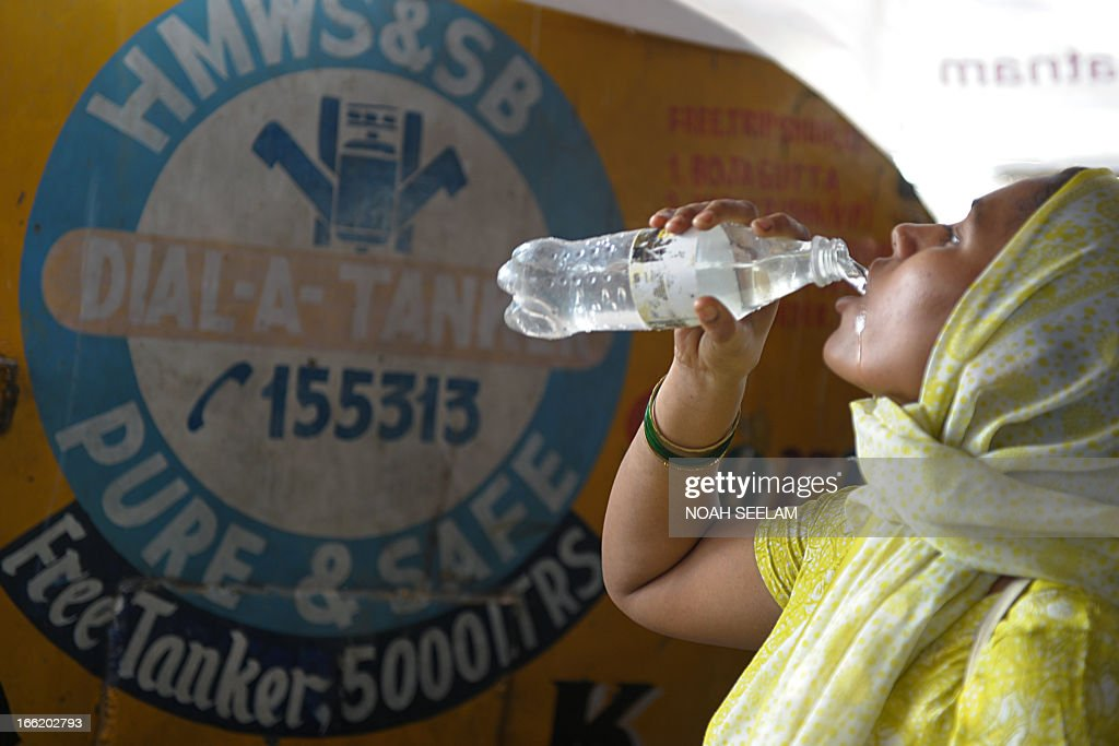 A resident drinks potable drinking water taken from a government water supply tanker at a slum in Hyderabad on April 10, 2013. Water shortages are a problem in the southern Indian city as summer temperatures soar above 40 degrees Celsius. AFP PHOTO / Noah SEELAM