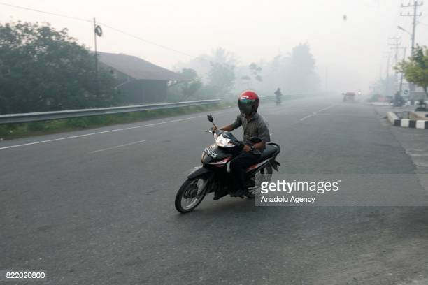 Resident drives motorcycle through haze from peat forest fire in Aceh Indonesia on July 25 2017 The number of hotspots in Indonesia continues to...