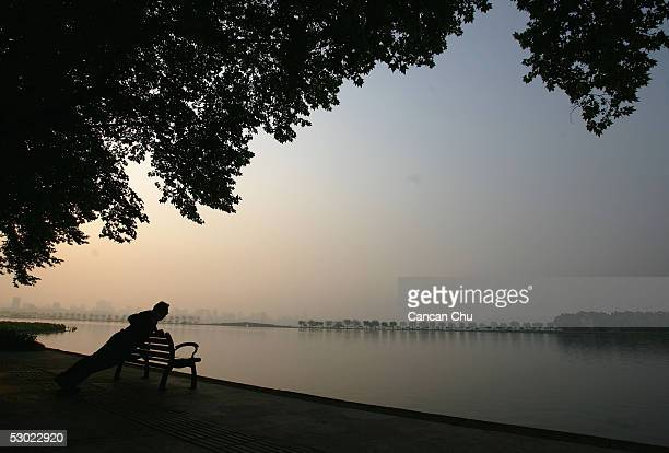 A resident exercises by the West Lake during the sunrise on June 3 2005 in Hangzhou Zhejiang Province of China The West Lake is one of China's most...