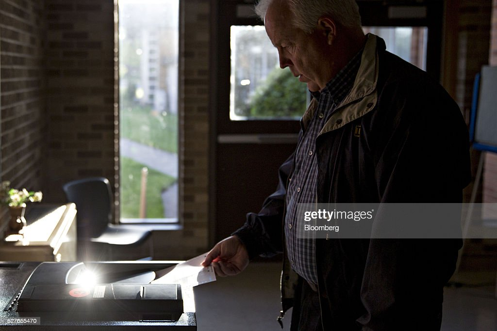 A resident feeds a ballot into a machine at a polling station during the presidential primary vote in South Bend, Indiana, U.S., on Tuesday, May 3, 2016. The outcome in Indiana, where balloting across two time zones will end at 7 p.m. Eastern time, could yield a deciding moment as the presidential race enters the home stretch. Photographer: Daniel Acker/Bloomberg via Getty Images
