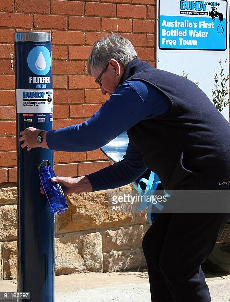 A resident fills a reusable plastic bottle from a new public drinking fountain on the first day of a bottled water ban in the Southern Highlands...