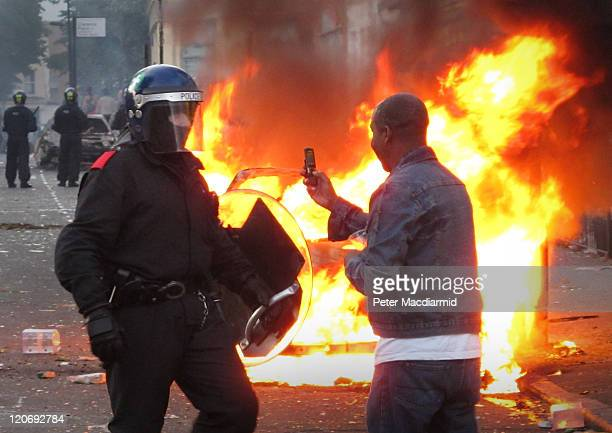 A resident films a police officer on his mobile phone during disturbances in Hackney on August 8 2011 in London England Pockets of rioting and...