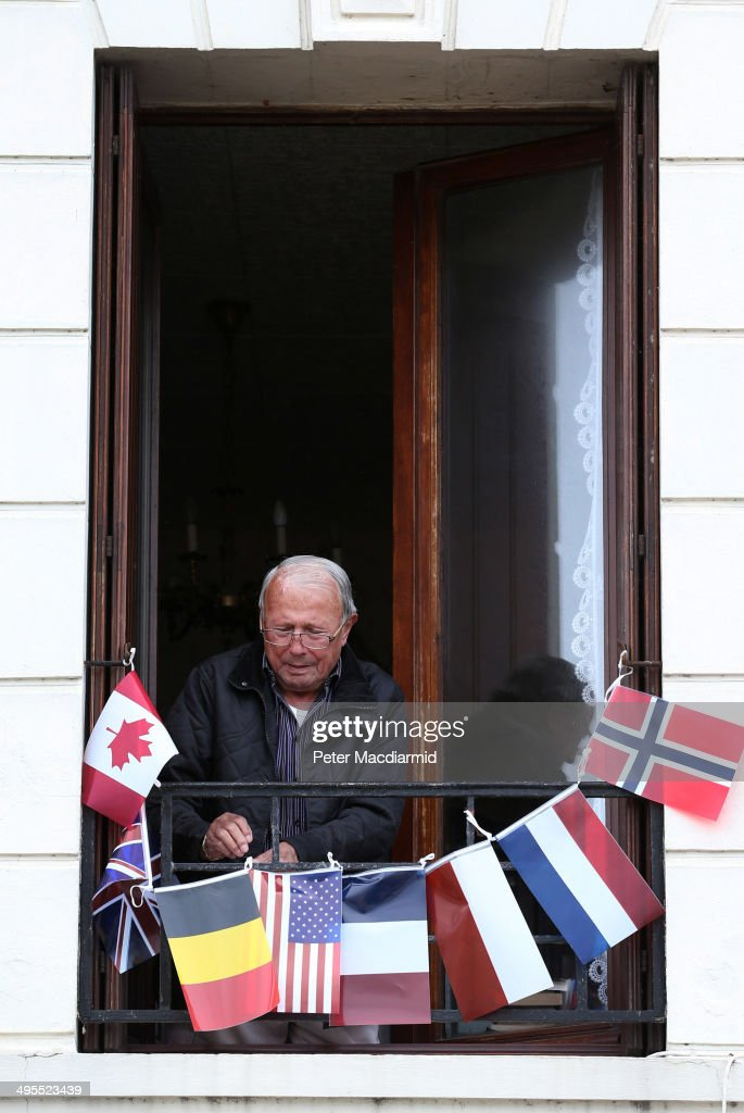 A resident fixes flags to his window on June 4, 2014 in Saint Aubin sur Mer, France. Friday 6th June is the 70th anniversary of the D-Day landings which saw 156,000 troops from the allied countries including the United Kingdom and the United States join forces to launch an audacious attack on the beaches of Normandy, these assaults are credited with the eventual defeat of Nazi Germany. A series of events commemorating the 70th anniversary are planned for the week with many heads of state travelling to the famous beaches to pay their respects to those who lost their lives.