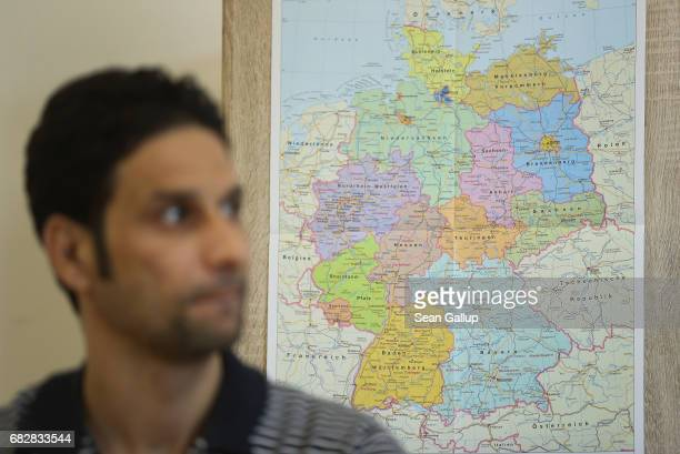 A resident from Iraq sits next to a map of Germany while attending instruction in Germany's democratic political system at a shelter for refugees and...