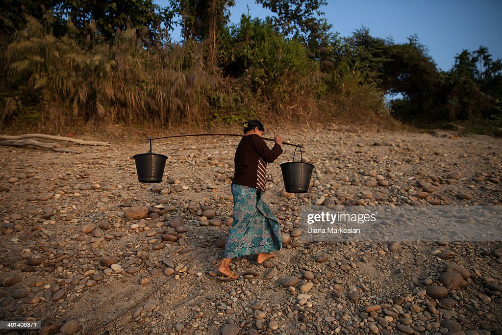 A resident from Kachin State carries buckets of water home on December 28, 2013 in Kachin State, Myanmar. The Irrawaddy River is the lifeline of Burma, running through the center of the country. The River provides vital nutrients to wetlands and floodplain areas downstream, including the delta region which provides nearly 60 percent of Burma's rice. A massive Chinese hydropower project is under construction in the Irrawaddy river, despite fierce opposition from the Kachin Independence Organization, which broke a 17-year-ceasefire after warning that it would fight to block the project. In 2011, the hydroelectric dam project was suspended under the mandate of President U Thein Sein. The project, which involves building a 152-meter-tall hydroelectric dam at the confluence of the two rivers that form the Irrawaddy, is the brainchild of a giant Chinese state-owned firm, China Power International.