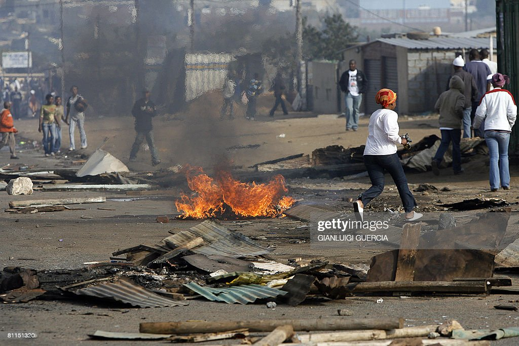 A resident from Reiger Park township run for cover on May 19 2008 as South African police shoot rubber bullets to disperse a crowd of rioters during...