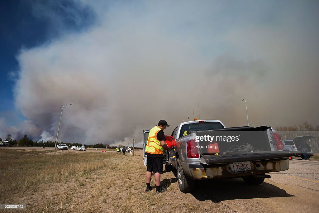A resident fuels up his truck at a roadblock as a wildfire burns south of Fort McMurray, Alberta, Canada, on Friday, May 6, 2016. The wildfires ravaging Canada's oil hub in northern Alberta have rapidly spread to an area bigger than New York city, prompting the air lift of more than 8,000 evacuees as firefighters seek to salvage critical infrastructure. Photographer: Darryl Dyck/Bloomberg via Getty Images